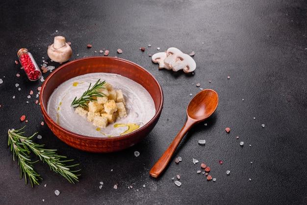 어두운 갈색 배경에 나무 숟가락으로 갈색 접시에 맛있는 아름다운 버섯 수프