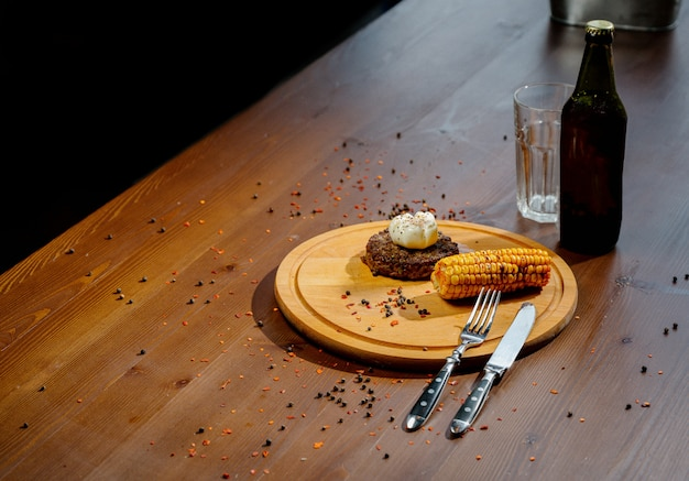 Вкусный стейк из говяжьего бургера со специями и зеленью на разделочной доске и шиферном столе. сочная жареная мясная котлета на деревянной разделочной доске