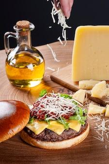 토마토 소스, 파르마 치즈, 양상추와 어두운 배경에 나무 테이블에 맛있는 쇠고기 햄버거. 공간 복사