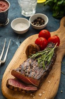 木製のまな板でおいしい牛肉ステーキ。チェリートマトとスライスした牛肉のグリルバーベキュー