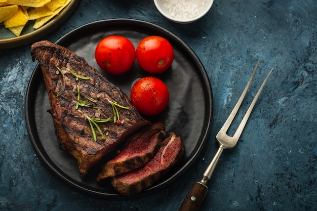 Delicious beef steak with salad, aromatic herbs, chery tomatoes
