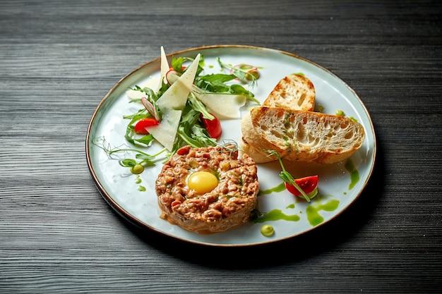 Вкусный тартар из говядины с желтком и гренками на тарелке. деревянный фон. выборочный фокус