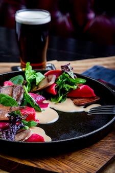 レストランでほうれん草とビーツのおいしい牛タン。大きな黒い大皿のクローズアップで健康的な高級食品