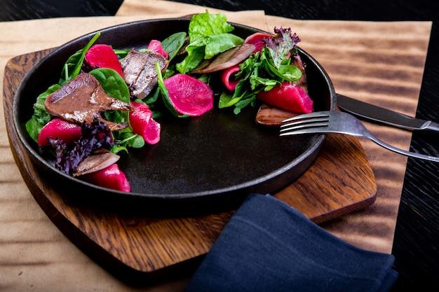 Вкусный говяжий язык со шпинатом и свеклой в ресторане