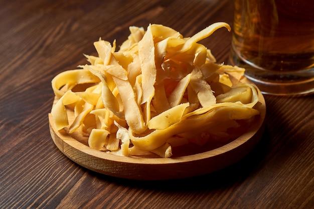 Вкусная закуска к пиву - вяленые и соленые кольца кальмаров в деревянной тарелке.