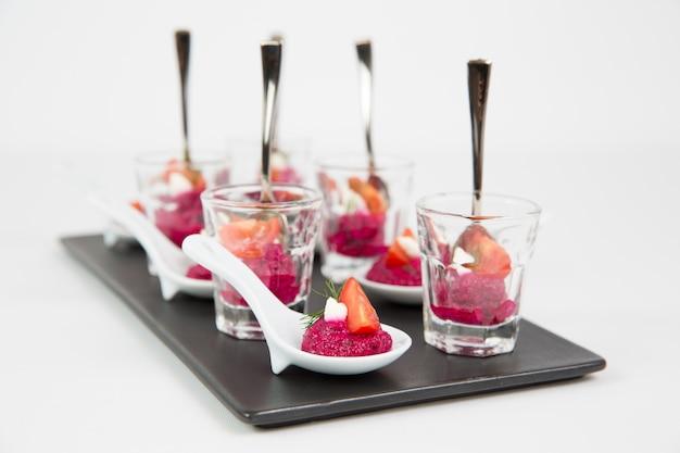 Вкусные свекольные соусы в прозрачных стаканах на черном керамическом подносе, изолированные на белом фоне