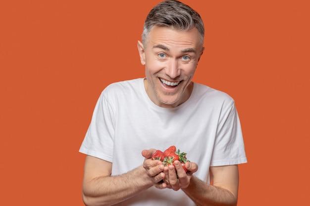 おいしいベリー。オレンジ色の背景に手のひらで熟した赤いイチゴを保持している夏のtシャツで歯を見せる笑顔で幸せな男