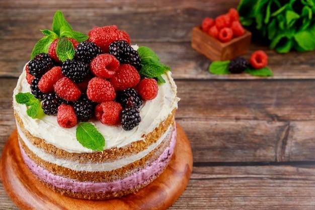 新鮮なラズベリーとブラックベリーで飾られたおいしいベリーケーキ。