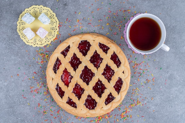 Deliziosa torta ai frutti di bosco, caramelle e tè sulla superficie di marmo