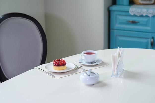 아늑한 카페에서 손님을 위해 테이블에 준비된 라스베리와 함께 맛있는 베리 차와 타르트