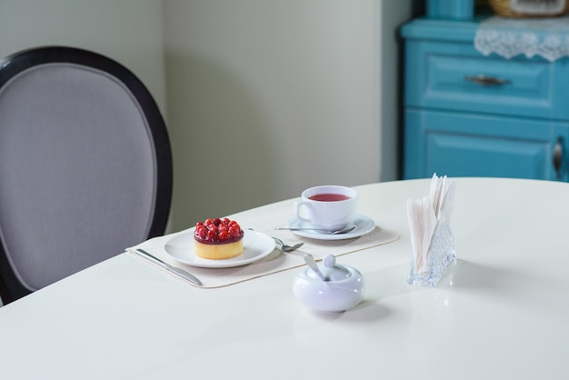 Delicious berry tea and tarte with raspberries prepared on a table for a guest in a cozy cafe