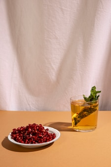 Delicious beverage with pomegranate seeds in front white curtain