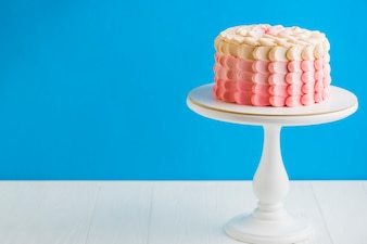 Delicious birthday cake with cakestand in front of blue wall