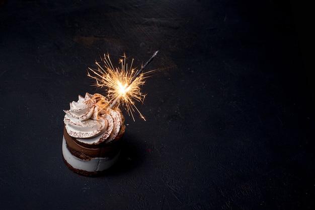 어둠에 대 한 테이블에 맛있는 생일 컵 케 익 불꽃 촛불
