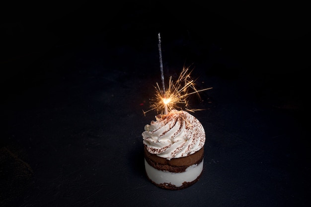 Delicious birthday cupcake with firework candle on table against dark background.