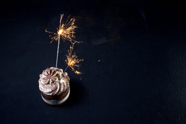 Delicious birthday cupcake with firework candle on table against dark background