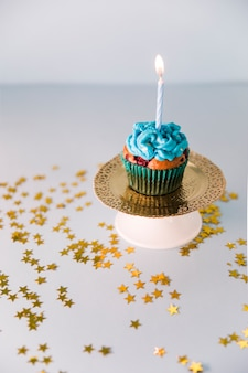 Delicious birthday cupcake with lighted candle on golden plate