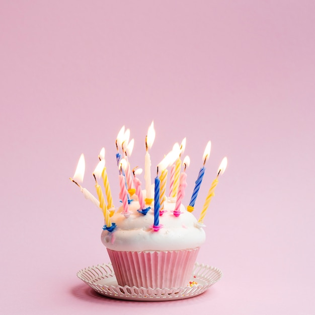Delicious birthday muffin with colorful candles