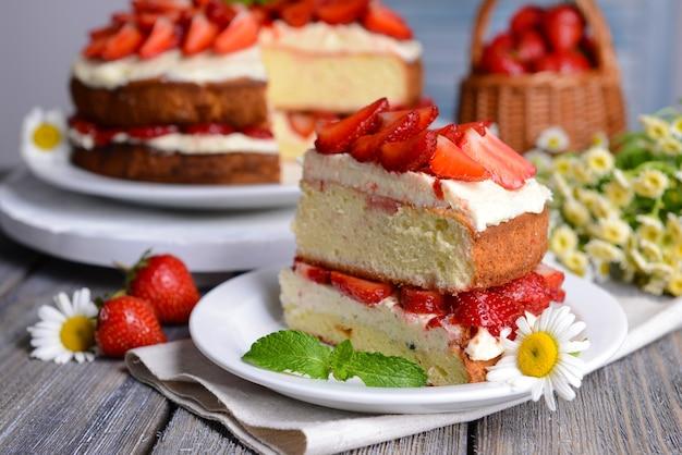 テーブルのクローズアップにイチゴとおいしいビスケットケーキ