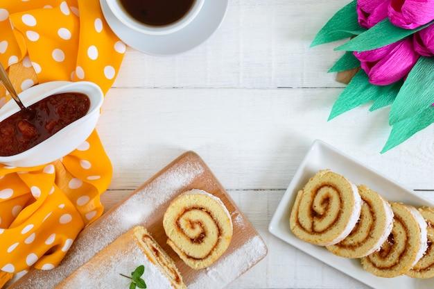 アプリコットジャムと紅茶のカップと白い木製のテーブルで美味しいビスケットロール。