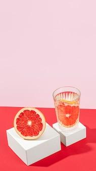 Metà arancia rossa deliziosa nell'angolo alto di vetro