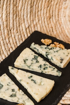 Delicious blue cheese arrange in a row over black slate