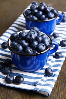 テーブルのクローズアップのカップのおいしいブルーベリー