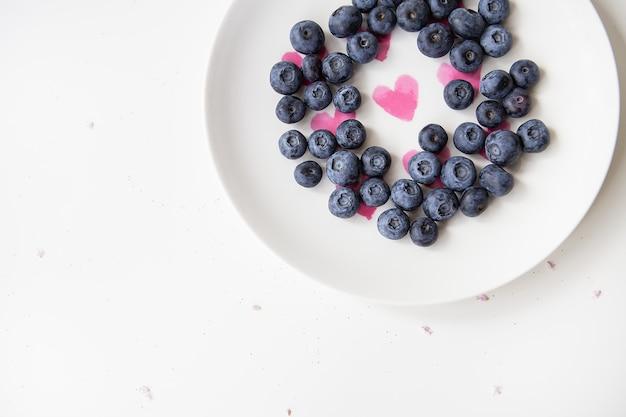 맛있는 블루베리는 내부에 하트가 있는 접시에 놓여 있습니다. 맛있고 건강한 음식. 비문에 대 한 장소입니다.