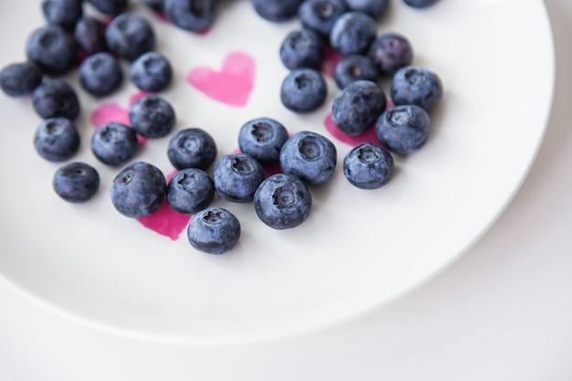맛있는 블루베리는 내부에 하트가 있는 접시에 놓여 있습니다. 맛있고 건강한 음식.
