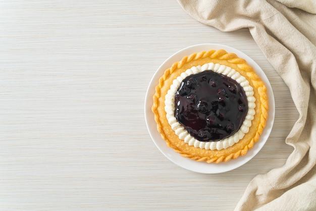 Вкусный пирог с черничным сыром на белой тарелке