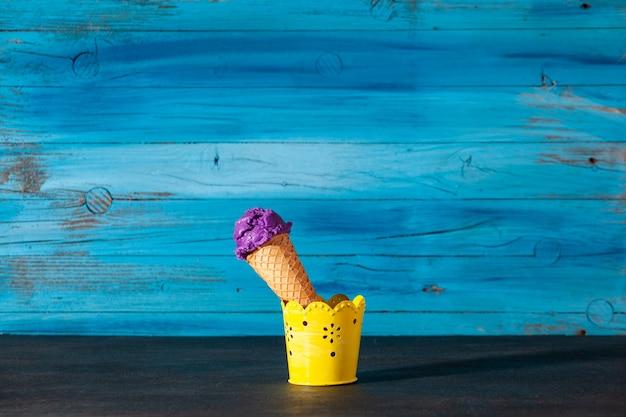 오래된 나무 파란색 벽에 맛있는 블루베리 아이스크림 콘