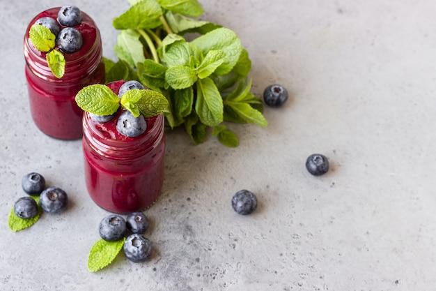 新鮮なベリーとミントのガラス瓶入りの美味しいブルーベリーのスムージー。夏の健康ドリンク。