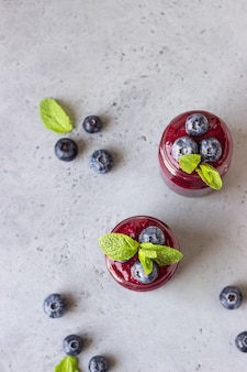 Delicious blueberry smoothie with fresh berries and mint in glass jars. summer healthy drink.