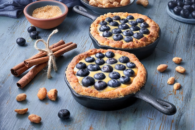 Delicious blueberry tartlets with vanilla custard cream on light blue