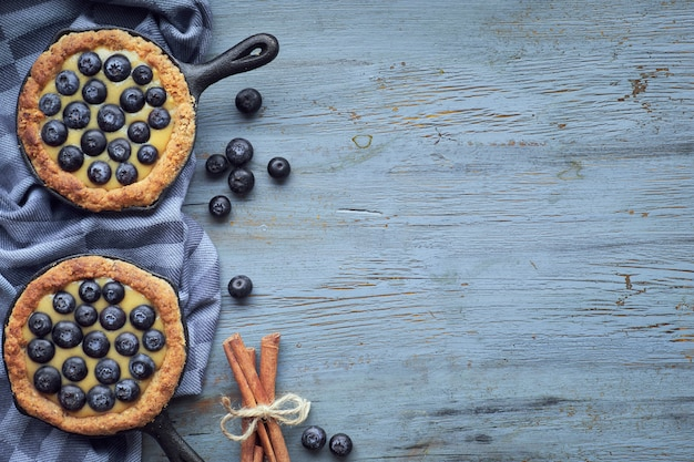 軽い素朴な木製のバニラカスタードクリームとおいしいブルーベリーのタルト