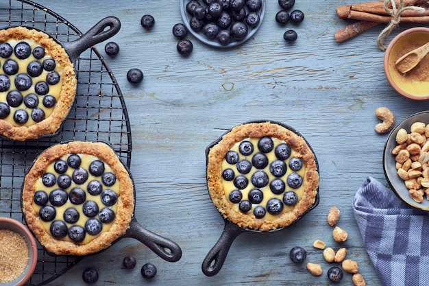 Delicious blueberry tartlets with vanilla custard cream on wood