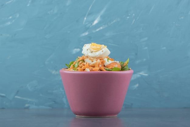 분홍색 그릇에 맛있는 삶은 계란과 신선한 샐러드.