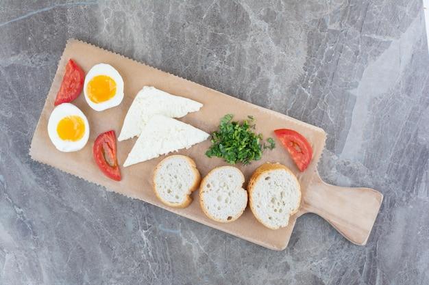 Вкусные вареные яйца с нарезанными помидорами и хлебом на деревянной доске. фото высокого качества