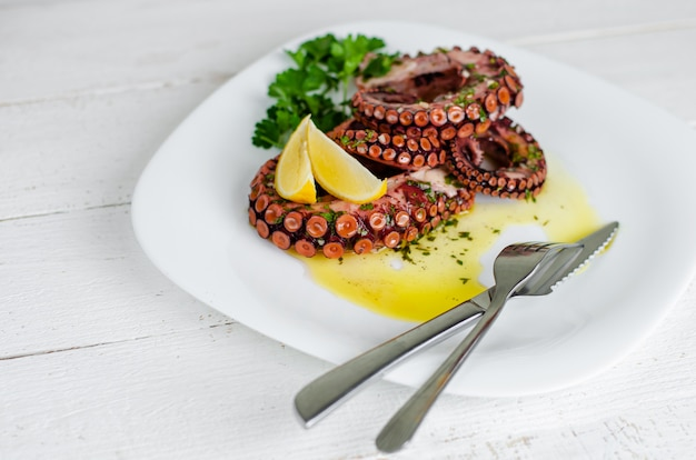 Delicious boiled octopus with lemon ,parsley and salad dressing on white plate. traditional mediterranean seafood