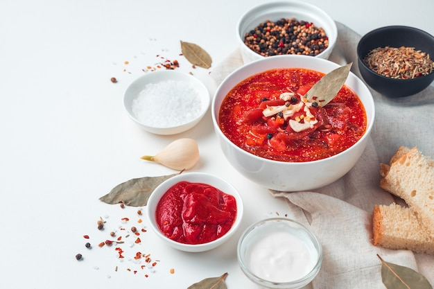 Delicious borscht with garlic and bay leaf on a white background.vegetable soup with tomato and beetroot, bread, garlic and sour cream on a white background.