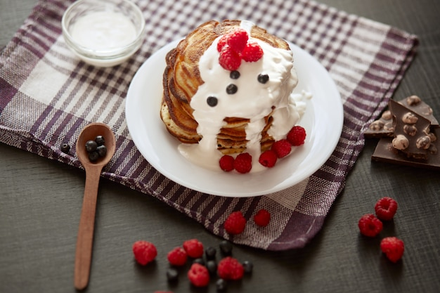 Delicious breackfast for family, pancackes with sour cream and berries, kitchen table decorated with raspberries, blueberries, wooden spoon