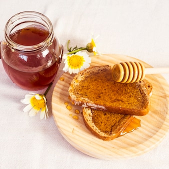 Delicious bread and honey in wooden plate