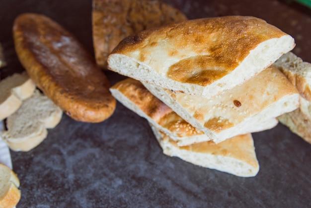 Delicious bread on slate board close up