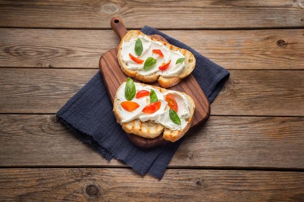 木製の背景にトマトとチーズのおいしいパン
