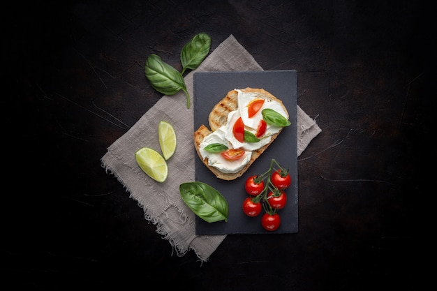 Delicious bread with cheese and tomato on a black background