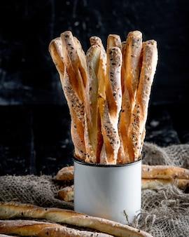 おいしいブレッドスティックグリッシーニ。イタリアの前菜。木製のテーブルと金属製のオールドスタイルのカップの黄麻布。