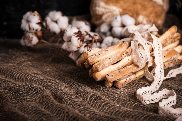 Delicious breadsticks grissini. italian appetizers. wooden table and burlap flowers of cotton and natural linen lace.