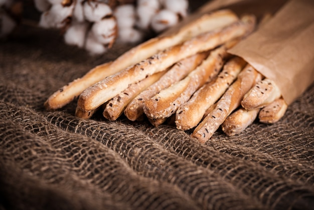 Delicious breadsticks grissini. italian appetizers. wooden table and burlap flowers of cotton.