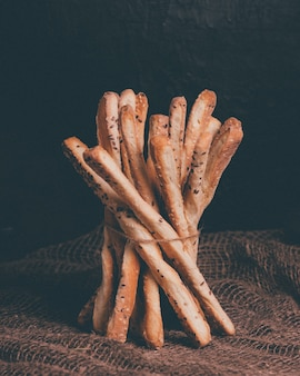 Delicious breadsticks grissini. italian appetizers. wooden table and burlap.