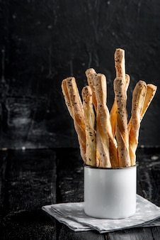 Delicious breadsticks grissini. italian appetizers. wooden table in metal oldstyle cup.